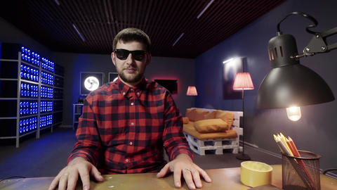 Adorable guy speaks, uses hand gestures looking at camera in furnished room Footage