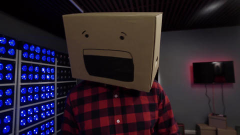 Male with put big carton box with drawn smile on his head and moves on camera Footage