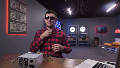 Man sticks wireless mic to shirt having box of power supply with cooler on desk Footage