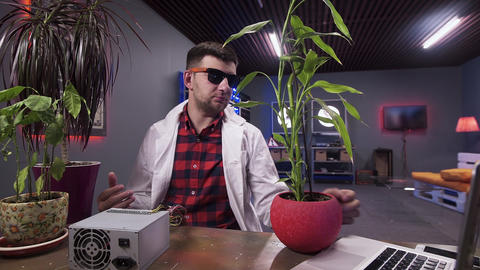 Man in white lab coat works on laptop behind desk with some plants in bowls Footage