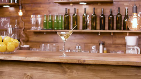 Parallax shot of a glass of martini beverage on a bar background Footage