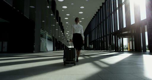 Business woman walking with wheeled bag Footage