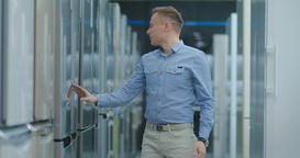 Handsome man in blue shirt open the refrigerator door in appliances store and Footage