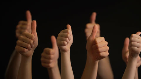Raising hands with thumbs up on black background Footage