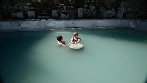 Couple Women Take Baths Near Antique Ruins. 4K Live Action