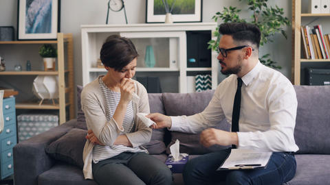 Helpful therapist comforting stressed woman crying in office giving paper tissue Footage