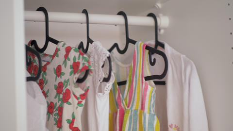 A close up of a baby girl clothes hanging in a wardrobe GIF