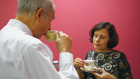 Senior couple drinking tea with cookie and talking. Elderly people lifestyle GIF