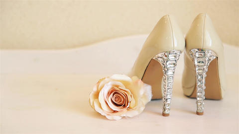 Wedding high-heeled shoes stand on a white chest of drawers with a rosebud beige Live Action