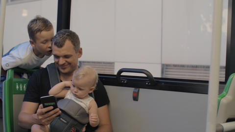 A man in a bus with a baby daughter and a son Footage