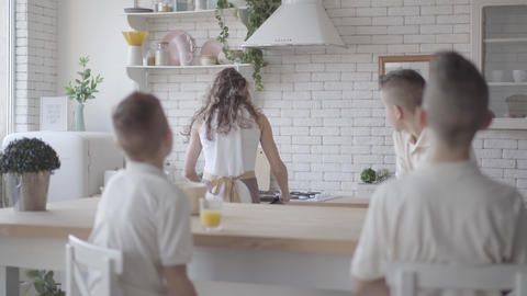Portrait young pretty mother bakes pies for her four teen sons in white shirts Footage