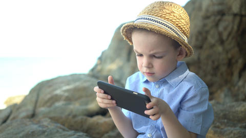 Cute boy sitting on a stone, using smartphone and looking at phone app near sea Footage