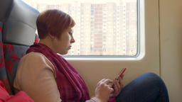 Woman scrolling and reading on her smartphone in the train Footage