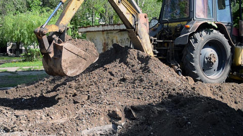 Tractor pits the ground. Backhoe piles up the ground close-up Footage