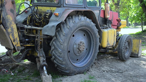 Tractor stands near ground pit. Backhoe piles up the ground close-up Footage