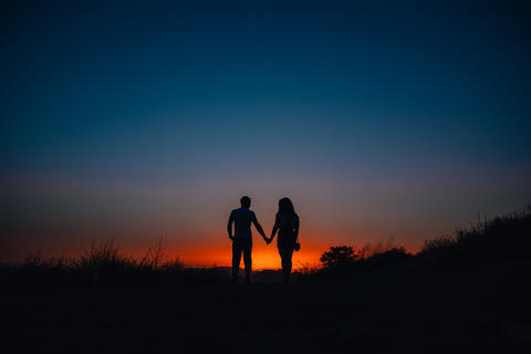 Young couple enjoying sunset in the mountains フォト