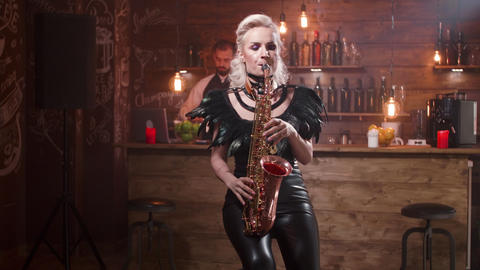 Young woman passionately playing a romantic song on a saxophone in front of a Live Action
