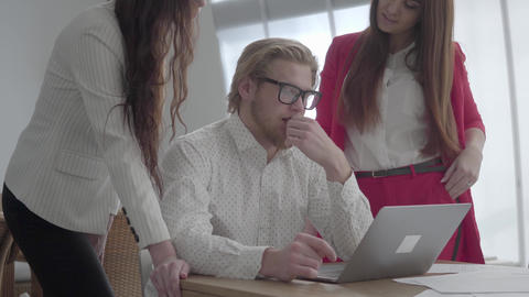 Portrait successful blond man in glasses sitting in a light comfortable office Footage