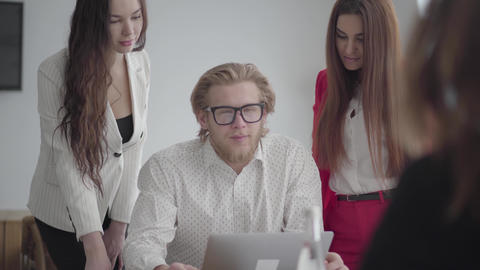 Blond man in glasses sitting in a light comfortable office with netbook at the Footage