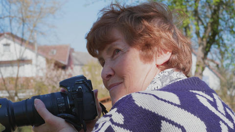 Senior woman taking photo on DSLR camera, smiling, outdoors Live Action