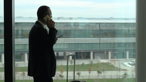 Passenger business man passenger at the airport by the window talking with phone Footage
