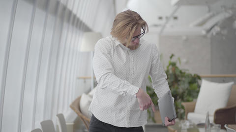 Blond happy man in glasses dancing in a light comfortable office holding gadget Live Action