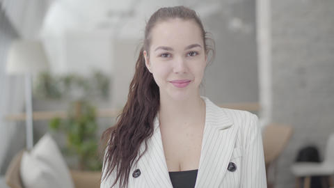 Portrait cute businesswoman standing in a light comfortable office looking at Footage