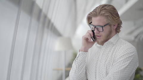 Handsome sad man in glasses standing in a light comfortable office talking by Footage