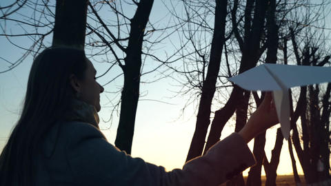 Woman running and launches paper airplane against sunset background. Concept of Footage
