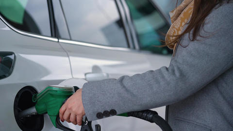 Woman fills petrol into her car at a gas station closeup ビデオ