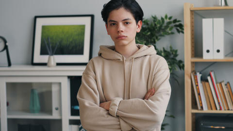 Portrait of serious teenager looking at camera with straight face at home Live Action