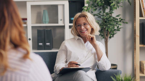 Positive psychoanalyst smiling laughing during conversation with female patient Footage