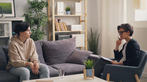 Emotional teen discussing troubles with young woman therapist in office Footage