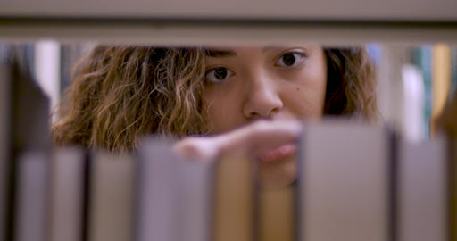 Multi-ethnic young woman in her early 20s or late teens selecting a book shot through a book shelf Footage