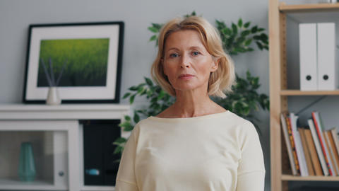 Portrait of emotionless mature woman looking at camera standing in office ビデオ