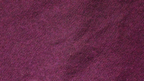Slow pan of a burgundy color polymer acrylic sweater in a textiles shop Footage
