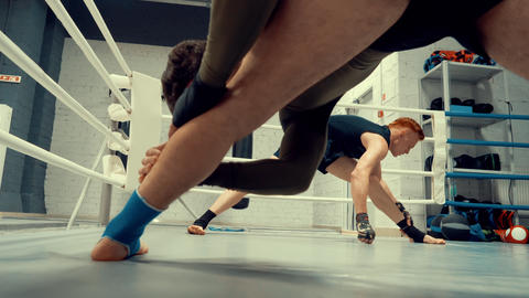 Fighters doing stretching legs before boxing training on box ring in fight club GIF
