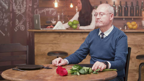 Sad old man sitting at a table in a restaurant and… Stock Video Footage