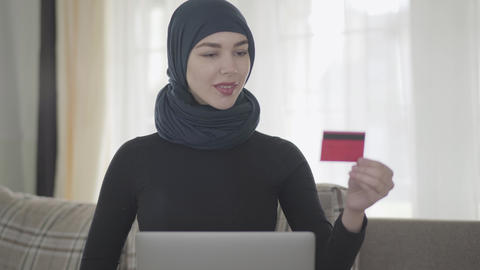 Portrait young smiling muslim woman using a credit card to pay online using Live Action