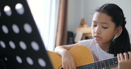 Asian little girl learning to play basic guitar by using acoustic guitar for beginner music Footage