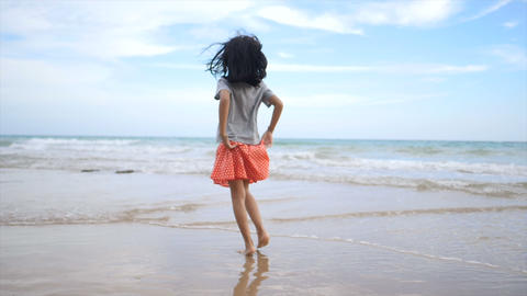 Asian little girl playing on the beach with nature sea wave coast for summer vacation concept2 Footage