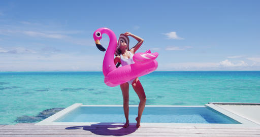 Vacation Woman in bikini and inflatable pink pelican toy mattress by pool Footage