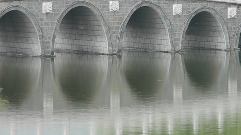 Arch bridge on lake in willows Park Stock Video Footage