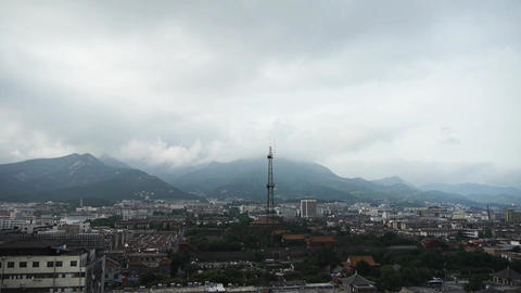 Clouds on top of hill,City buildings relying on... Stock Video Footage