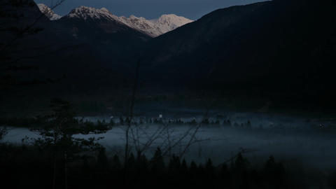 Timelapse - Snowy mountains above the misty valley at dawn Footage