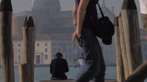 Couple sitting on the pier and drinking alcohol. Venice, Italy GIF