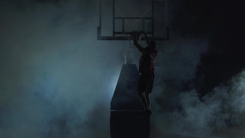 Healthy young man playing basketball in black background with clouds of smoke Acción en vivo