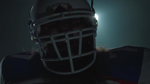 Close-up portrait of american football player in sports equipment and helmet Footage