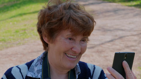 Emotional senior woman talking via mobile video, smiling Footage