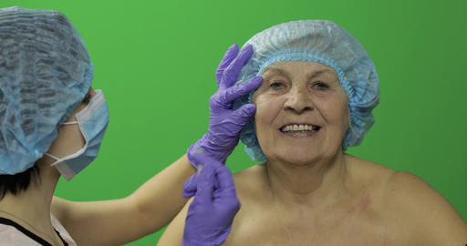 Elderly female in protective hat. Doctor making facial injections for patient Footage